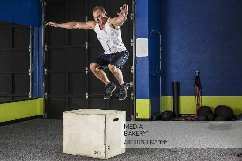 Full length shot of muscular man performing box jump in gym