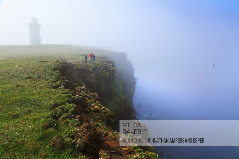 Family visiting Langanes peninsula and lighthouse during foggy weather, Iceland