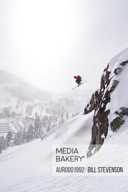 Skier jumps off a snowy cliff.