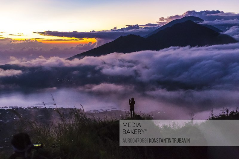 Man takes photos with smartphone in mountains at sunrise