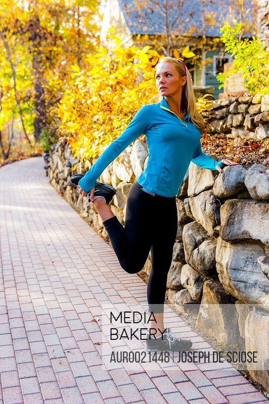 A 39 year old blond woman wearing fitness clothing stretching on a sidewalk in a suburban environment.