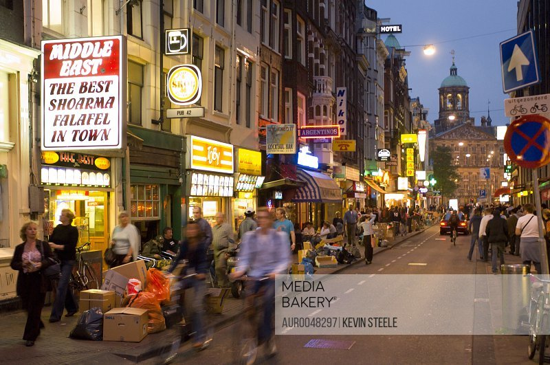 A typical Summer evening in the center of Amsterdam, The Netherlands (Holland). The busy street leads to the Royal Palace on Dam Square in the background.<br><br><span style='color: red'>Editorial Use Only.</span><br><br>