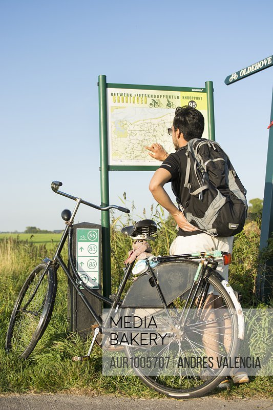 A young man wearing sunglasses, standing next to his bike, uses a map to find his way in  the province of Groningen, The Netherlands, around the Netwerk Fietsknooppunten, a network of marked junctions of bycicle roads spanning all country Netherlands.