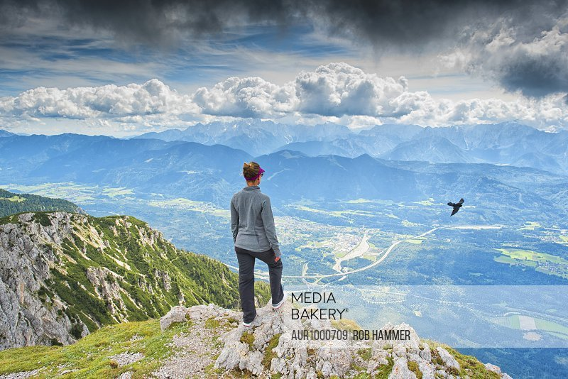 A girl standing on top of the Dobrach in Austria overlooking a vast mountain range.