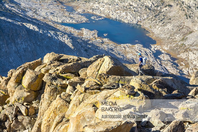A man hiking along the summit of Mount Mendel along the 8.5 mile Evolution Traverse, John Muir Wilderness, Kings Canyon National Park, Bishop, California.