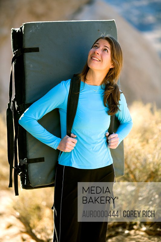 Female climber with a crash pad.