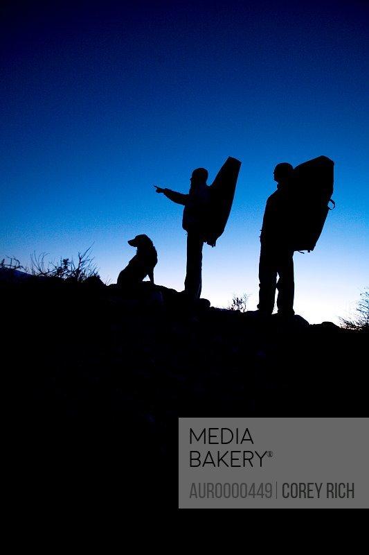 Man, woman and dog hike with crash pads