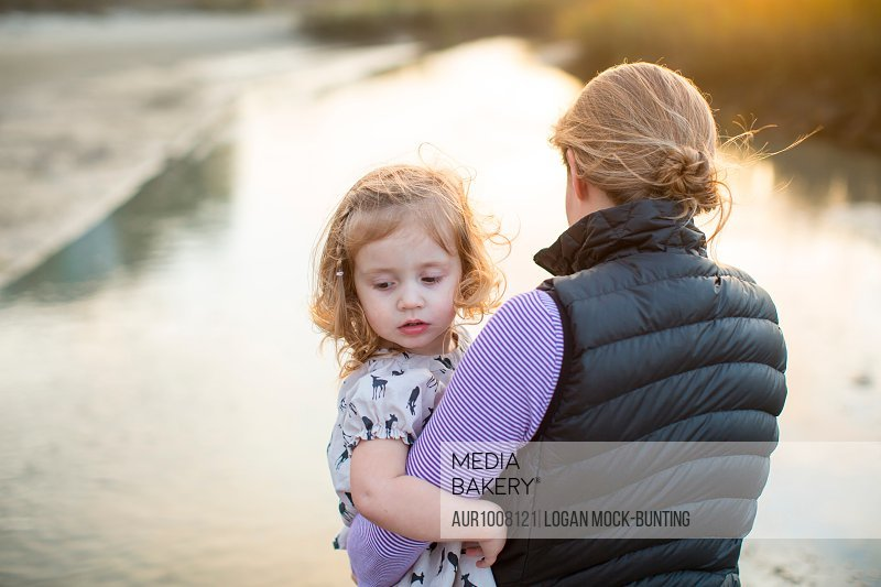 A woman carrying her daughter in her arms in a marsh at Wrightsville Beach, NC.