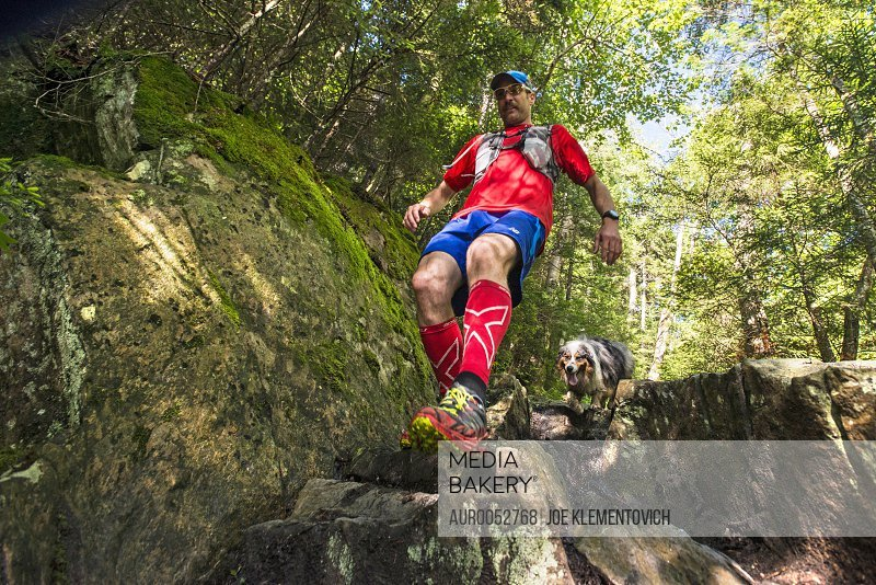 Man With His Dog Moving Down On Rocky Slope In Forest
