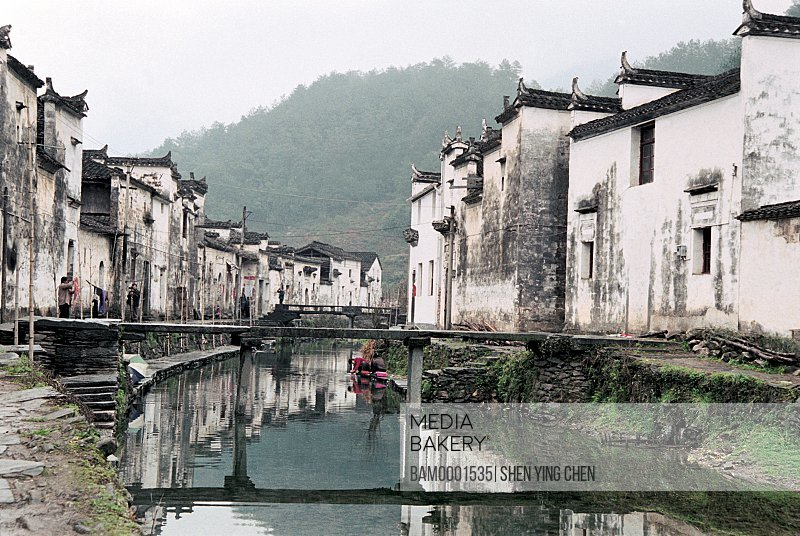View of houses by canal with mountains in the background, Ming and Qing dynasty historic building of Likeng village, Jiangling Village, Wuyuan County, Jiangxi Province of People's Republic of China