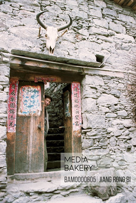 Portrait of a man standing by door, The Zang minority people's house in Ganbao Zang minority village, Li County, Aba State, Sichuan Province of People's Republic of China