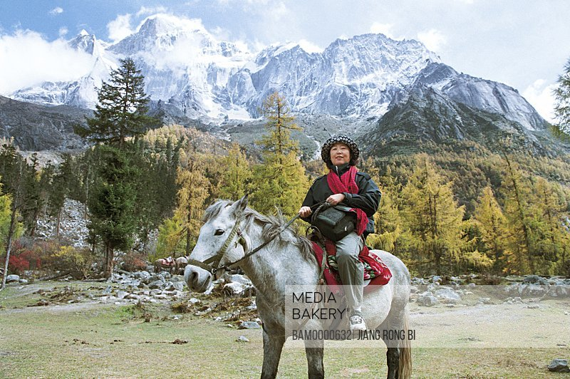 View of a tourist sitting on horse with mountains in the background, Siguniang Mountain, Xiaojin County, Aba State, Sichuan Province of People's Republic of China