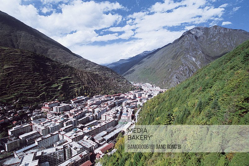 Cityscape with mountains against blue sky, To see Kangding County on Paoma Mountain, Kangding County, Ganzi State, Sichuan Province of People's Republic of China