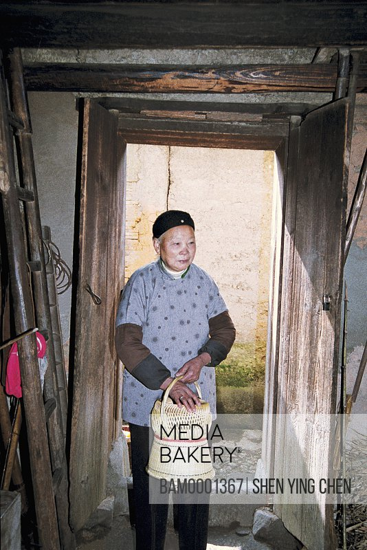 View of a senior woman holding a handbasket, The old men warmed by a fire the basket at old Heping town in Shaowu, Heping town, Shaowu County, Fujian Province of People's Republic of China