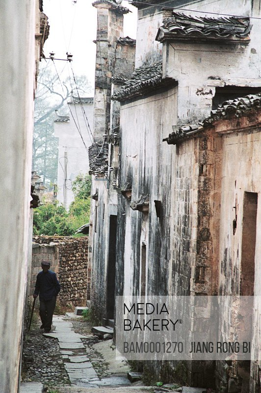 Man walking on alleyway amid houses, Alleyway in Ancient Pingshan Village, Yixian County, Anhui Province, PRC