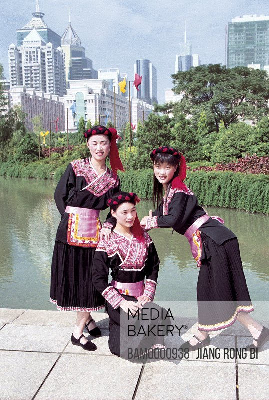 Portrait of three teenage girls standing by lake with buildings in the background, She minority women at the photographic exhibition often Taiwan strait, Fuzhou City, Fujian Province, People's Republic of China