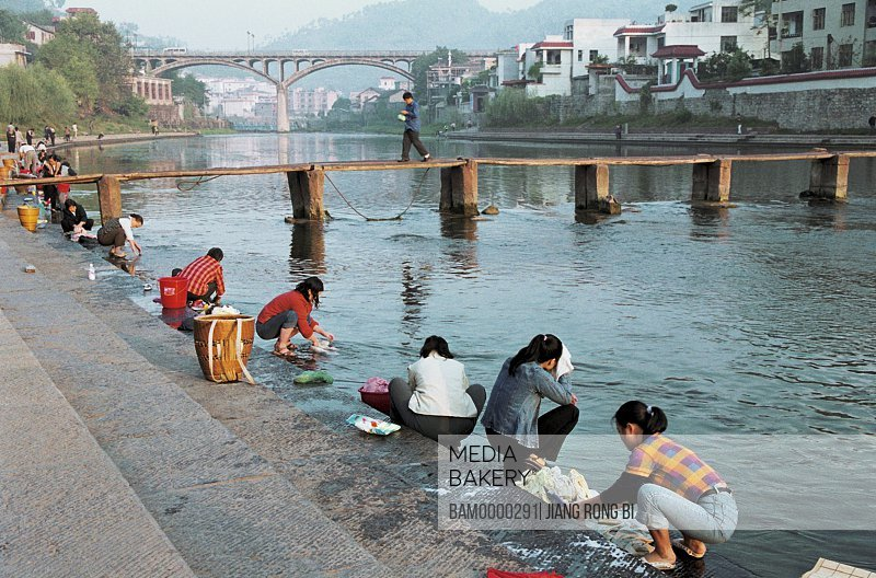 Women washing clothes at a bank of the Tuo river, Fenghuang, Xiangxi Prefecture, Hunan Province, People's Republic of China