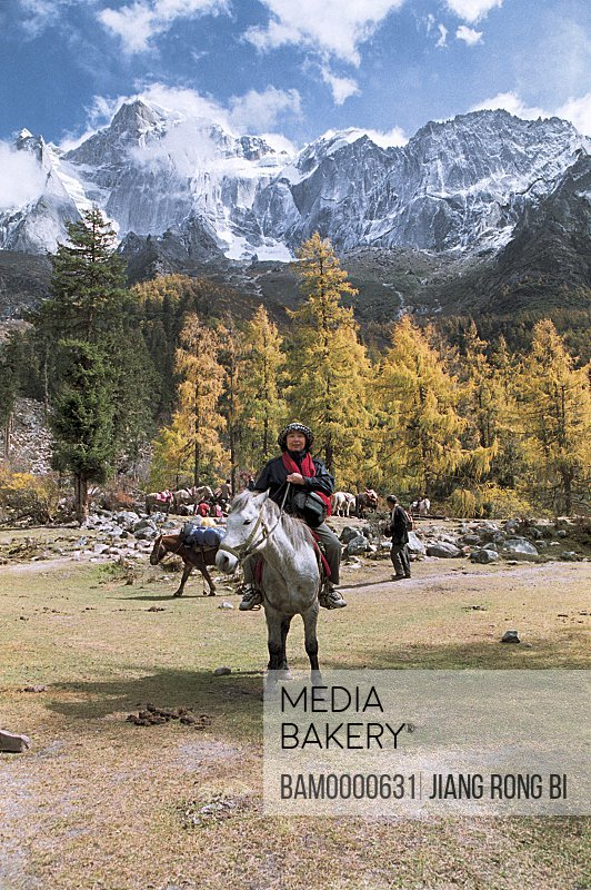 View of tourist sitting on horse with mountains in the background, Siguniang Mountain, Xiaojin County, Aba State, Sichuan Province of People's Republic of China