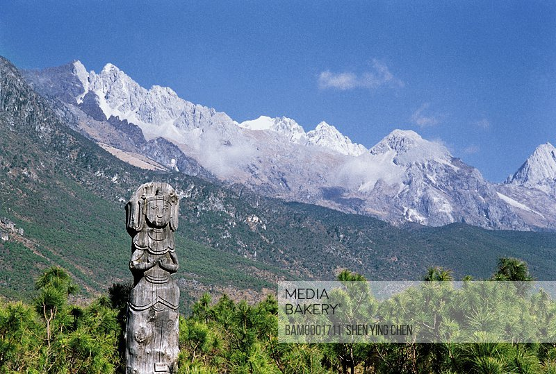 Wooden sculpture with mountains in the background, Dongba God Gardon and scenery of the Yulong Snowy Mountain, Dongba Village, Lijiang City, Yunnan Province of People's Republic of China