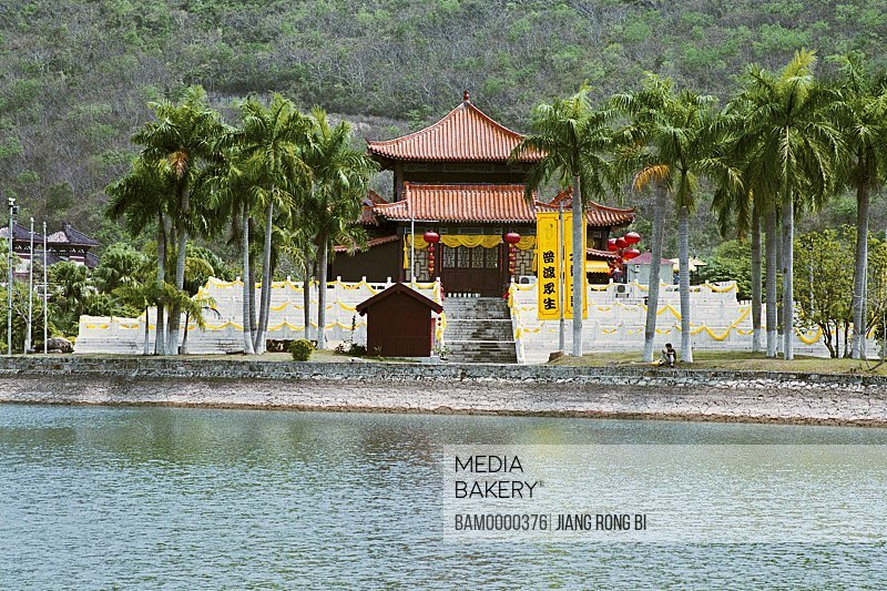 View of a shrine amid palm trees by lake, South Mountain Temple, Sanya City, Hainan Province of People's Republic of China