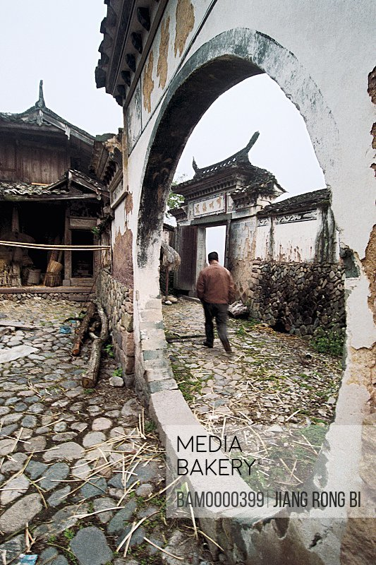 Rear view of a man in alley through circular entranceway, Ancient Residence in Taishun, Taishun County, Zhejiang Province, People's Republic of China