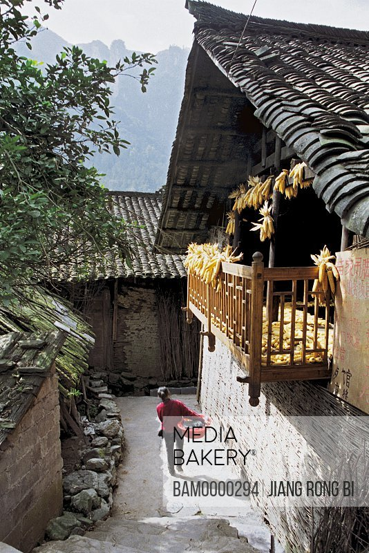 Woman walking with a basket on small street, The small street in theMiao minority housing of Dehang, Jishou City, Xiangxi Prefecture, Hunan Province, People's Republic of China