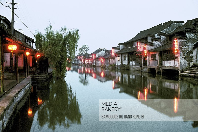 View of illuminated houses by river at dusk, The night scenery of Xitang region of rivers and lakes pond, Xitang Town, Jiashan County, Jiaxing City, Zhejiang Province of People's Republic of China