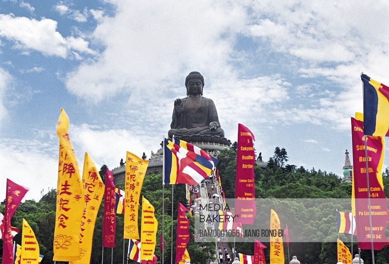 Low angle view of statue with flags in foreground, The Tiantan buddhu in the Dayu Mountain, Hongkong special administration region of People's Republic of China