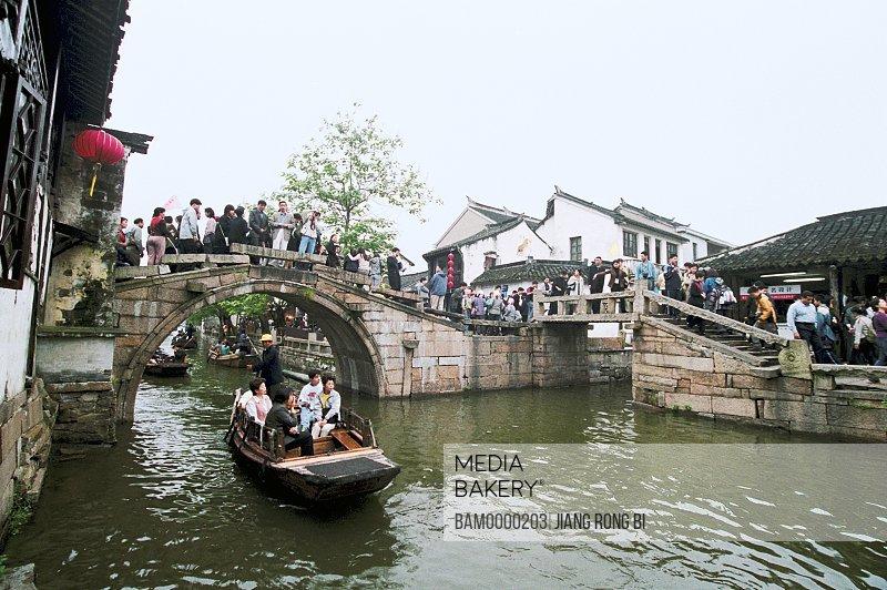 Tourists traveling on boat, Crowded-visitor's Zhouzhuang double bridge, Zhouzhuang Town, Kunshan City, Jiangsu Province of People's Republic of China