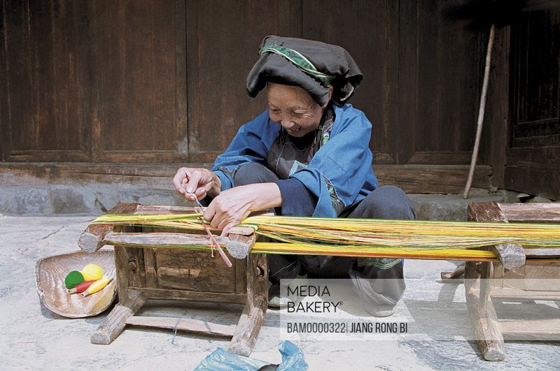 Cheerful Miao minority older woman making a brocade in Miao minority housing of Dehang, Jishou City, Xiangxi Prefecture, Hunan Province, People's Republic of China