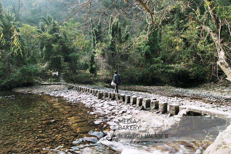 View of a man walking on rocks, Bank of Nanxi River, Nanxi River, Yongjia County, Zhejiang Province, People's Republic of China