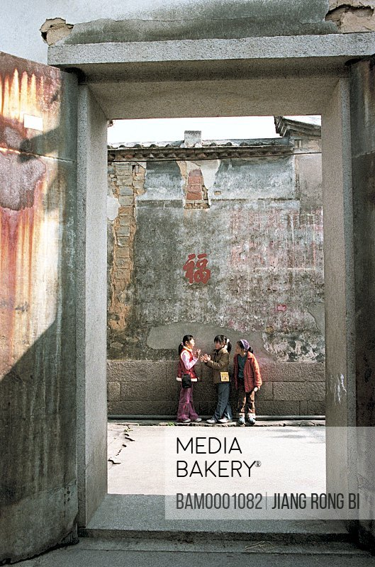 View of girls standing against wall, The girl in the Man nationality village in Qinjiang of Changle, Changle, Fuzhou City, Fujian Province, People's Republic of China