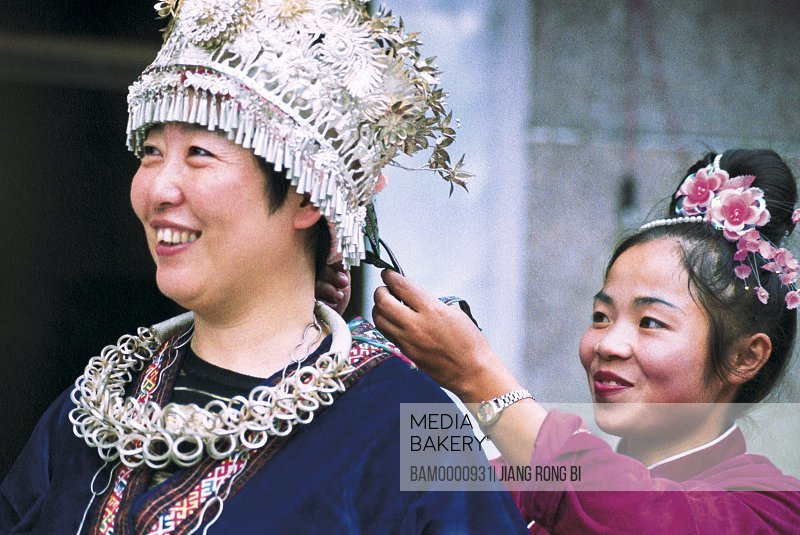 Miao minority girls are helping the tourists wearing the national clothing, Anshun City, Guizhou Province of People's Republic of China
