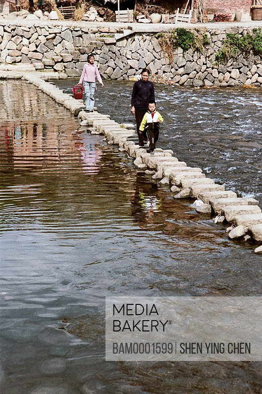 Mother and children crossing stone bridge across a stream, The Villagers and Village of the Shouning County, Shouning County, Fujian Province of People's Republic of China