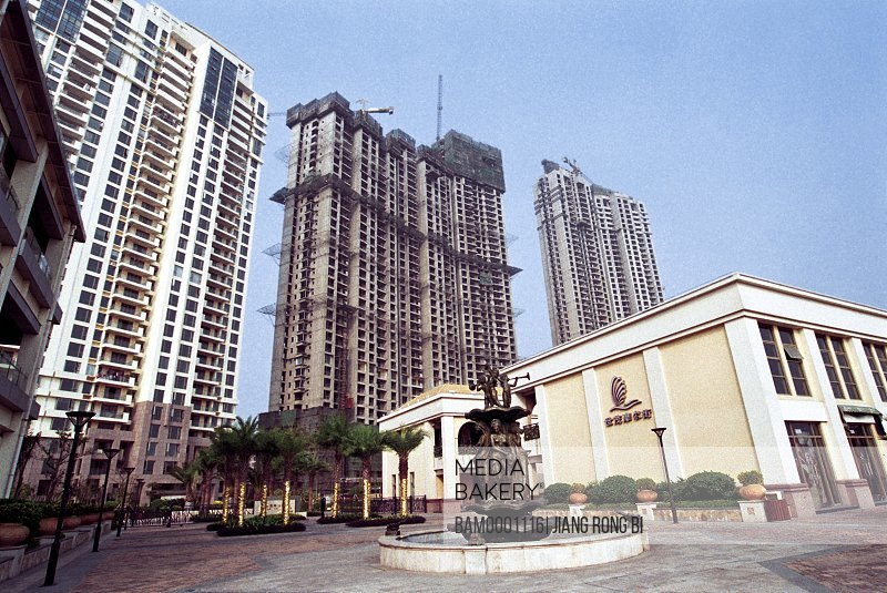 Low angle view of statue with buildings in the background, Mo'er street in the outward beach garden of Shimao, Fuzhou City, Fujian Province, People's Republic of China
