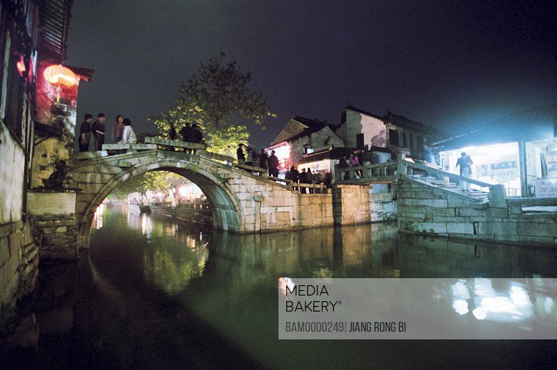 View of tourists standing on bridge over lake at night, The night scenery of double bridges of Zhouzhuang region of rivers and lakes pond, Zhouzhuang Town, Kunshan City, Jiangsu Province, People's Republic of China
