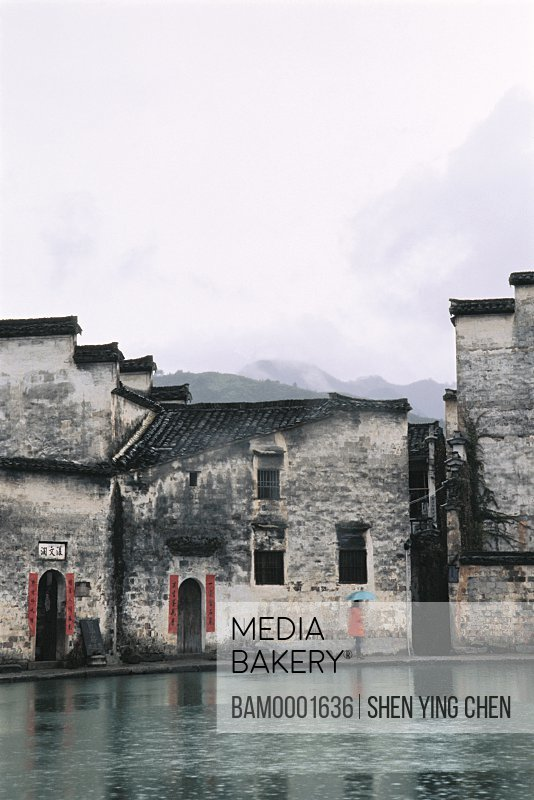Person with umbrella standing on sidewalk by buildings, Hong Village's ancient common people residence of Ming and Qing dynasty, Hong Village, Yi County, Anhui Province of People's Republic of China