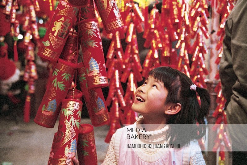 View of a cheerful girl looking at crackers, Nanhou street, Fuzhou City, Fujian Province, People's Republic of China