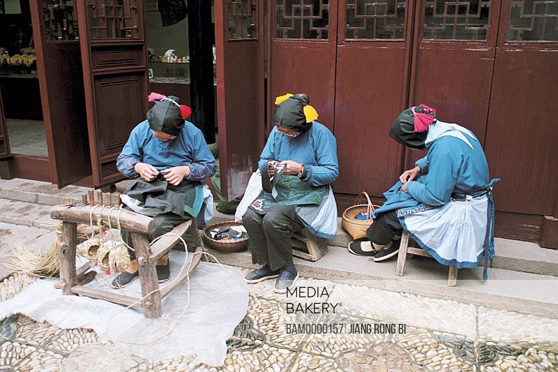 Women working outside a house, The Hand-planted folk custom clothing made by woman of Jiaozhi region of rivers and lakes pond, Jiaozhi Town, Kunshan City, Jiangsu Province of People's Republic of China