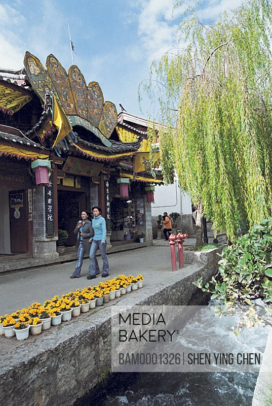 Friends walking by shop, Historic building of old Lijiang city, Lijiang old city, Yunnan Province of People's Republic of China