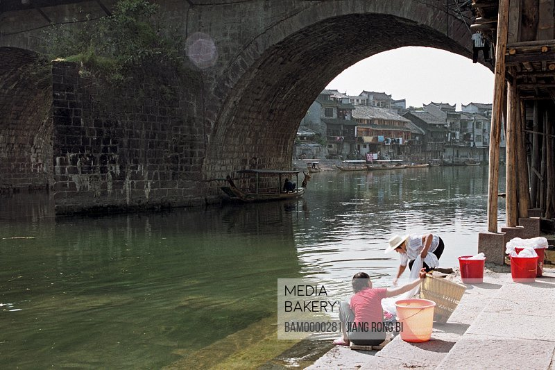 Women washing clothes on riverbank, under the Wohong bridge in the old city, Fenghuang, Xiangxi Prefecture, Hunan Province, People's Republic of China