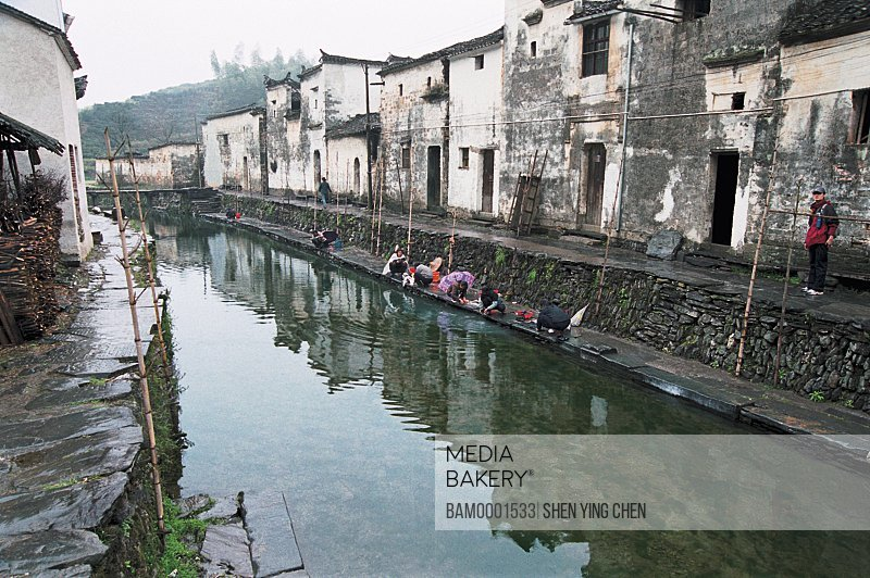 View of people washing clothes by canal, Ming and Qing dynasty historic building of Likeng village, Jiangling Village, Wuyuan County, Jiangxi Province of People's Republic of China