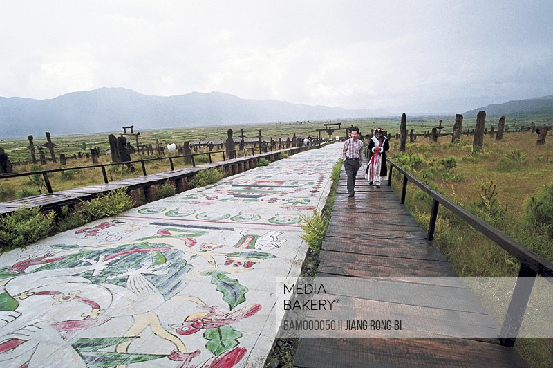 Man and woman walking on wooden planks by paintings, Gallery of Dongba Park, Lijiang City, Yunnan Province, People's Republic of China