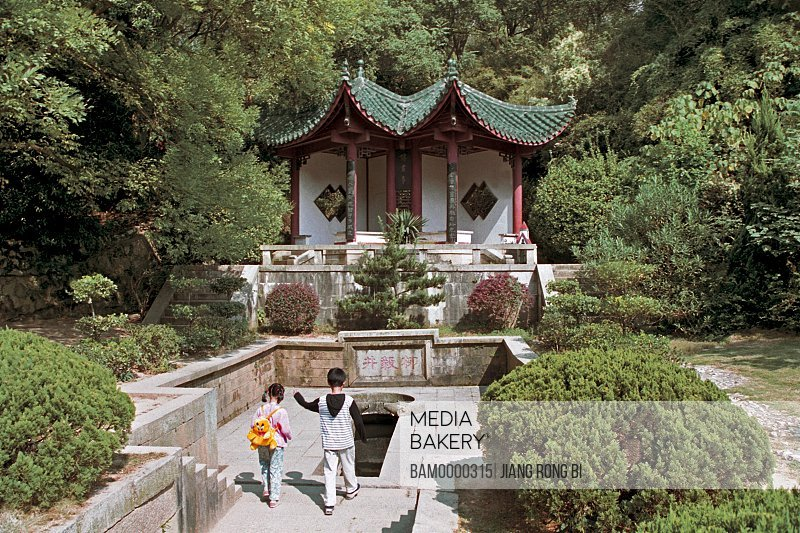 View of children walking in front of Liuyi well, in the park of Jun Mountain, Yueyang City, Hunan Province, People's Republic of China