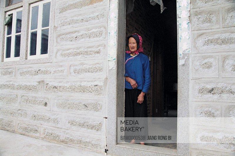 Senior woman standing by door, Old Huian Ladies in Xiaozuo Village, Chongwu Town, Huian County, Fujian Province, People's Republic of China