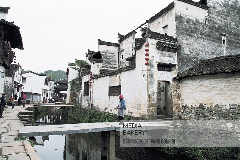 Person walking on bridge by houses, Ancient common people residence of Huipai in Likeng Village, Likeng Village, Wuyuan County, Jiangxi Province of People's Republic of China