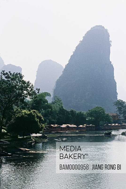 View of a river with mountain in the background, The scenery of Yulong river, Yangshuo, Yangshuo County, Guilin City, Guangxi Zhuang Nationality Autonomous Region of People's Republic of China