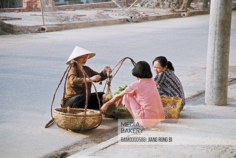 View of a peddler selling vegetables to women, Xialongwan, Xialong City, Guangning Province, Vietnam
