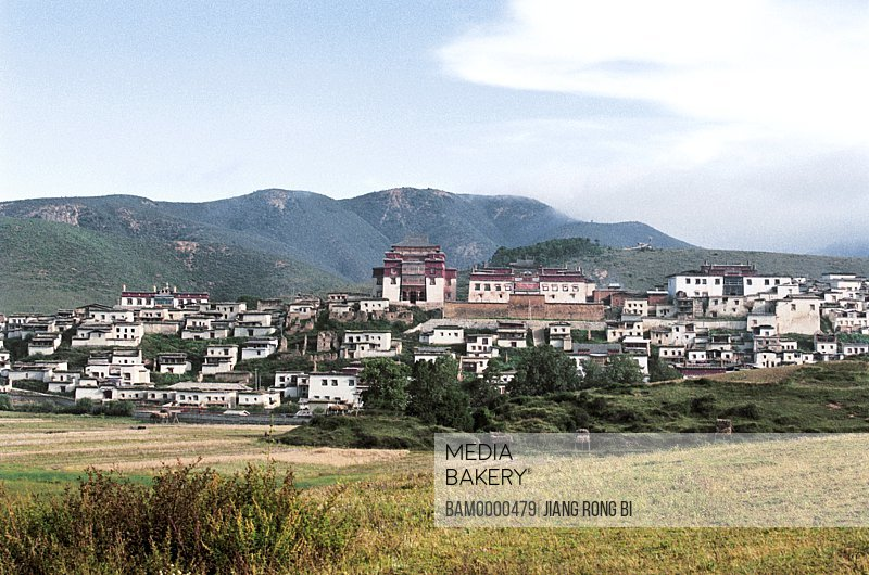 View of houses with mountains in the background, Gedan Songzanlin Lamasery Built in Year 1679, Shangri-la County, Diqing Prefecture, Yunnan Province, People's Republic of China