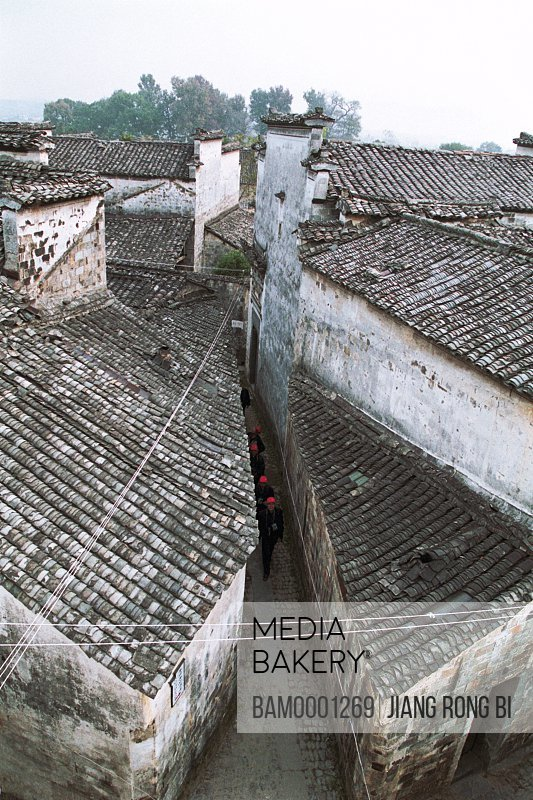 People walking on alleyway amid houses, Alleyway in Ancient Pingshan Village, Yixian County, Anhui Province, PRC